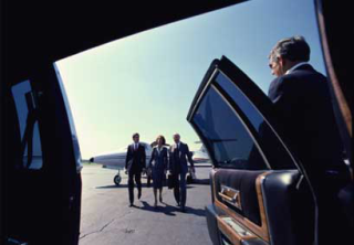 Executive clients approach an escort car door, being held for them by a security agent